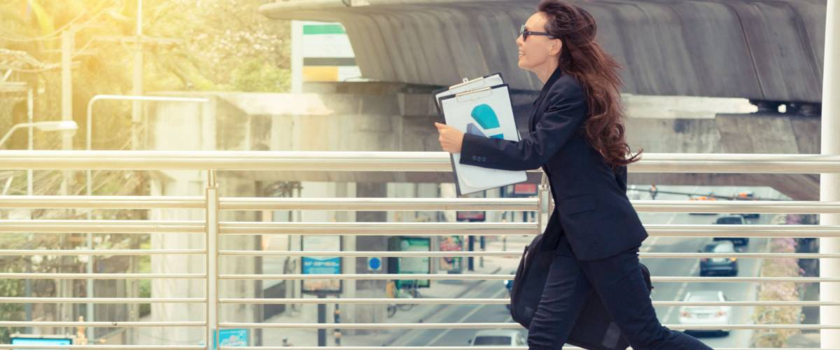 Blurred motion of Energetic business woman is running with carrying a briefcase to a business meeting. Competition concept.