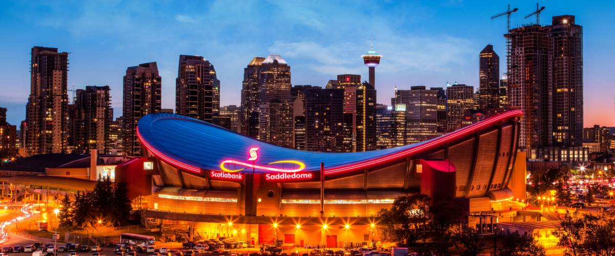 CALGARY, CANADA - MAY 23, 2015:  Panorama of Calgary downtown skyline at sunset blue hour showing the iconic Scotiabank Saddledome and Calgary Tower with surrounding city skyscrapers.