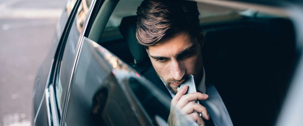 pensive young man in the back of a car holding a mobile phone