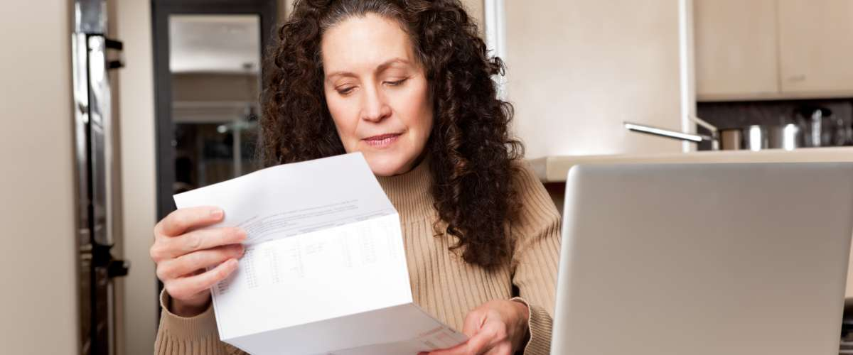 middle aged woman paying bills at home