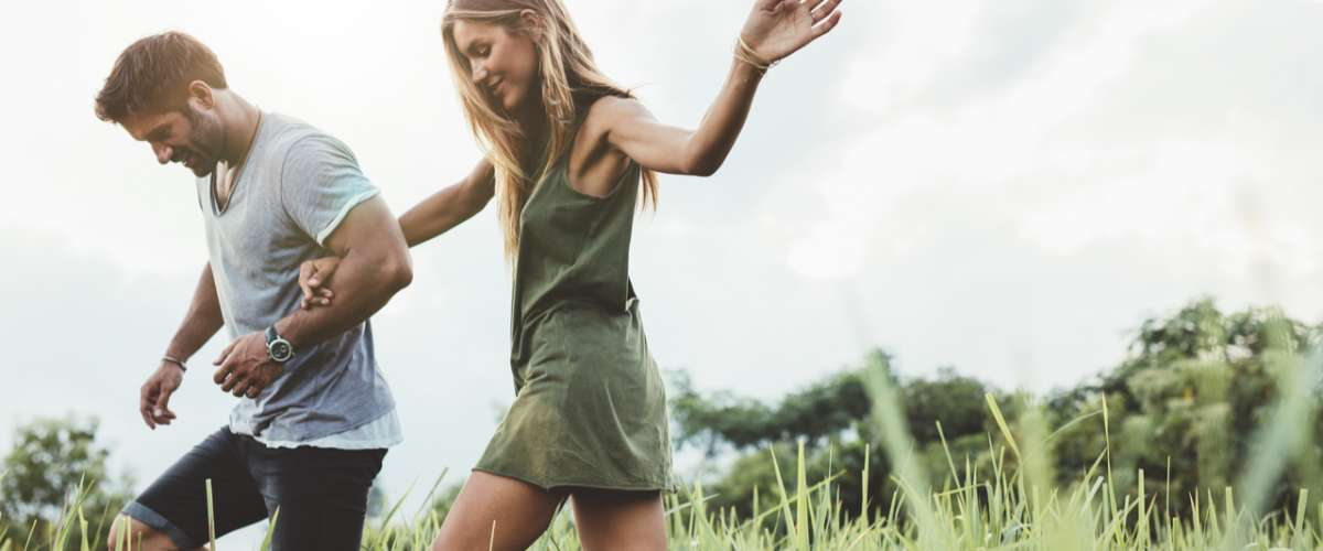 outdoor young stylish couple walking through meadow hand in hand