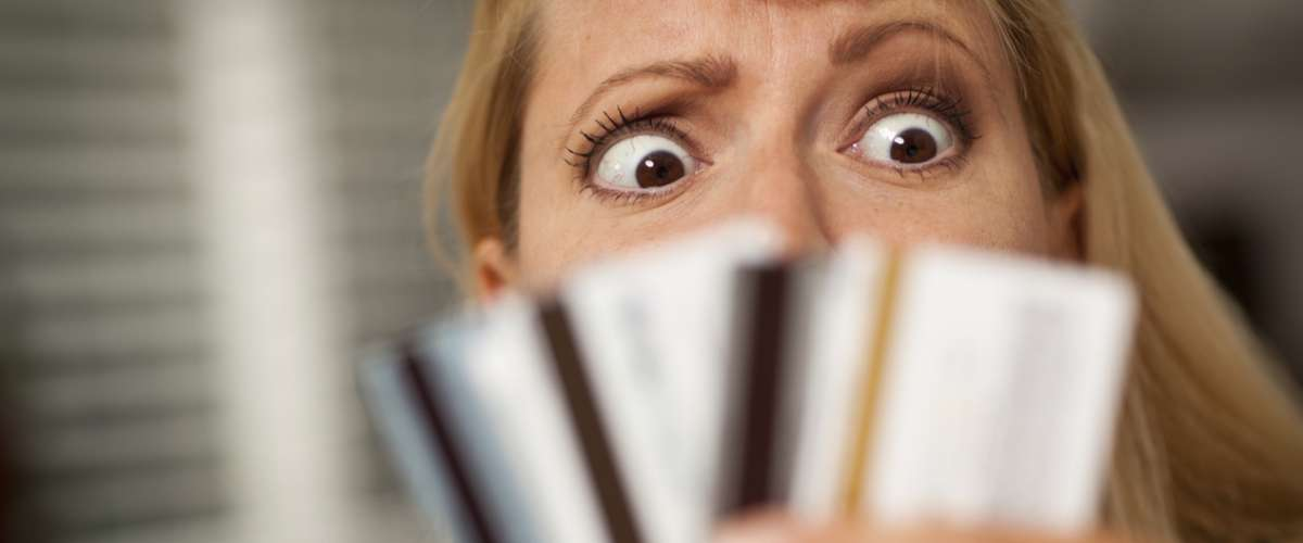 Woman staring at her many credit cards looking perplexed