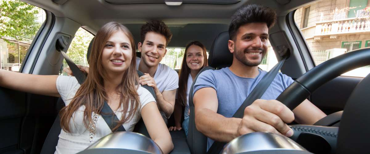 Group of happy young friends in a car