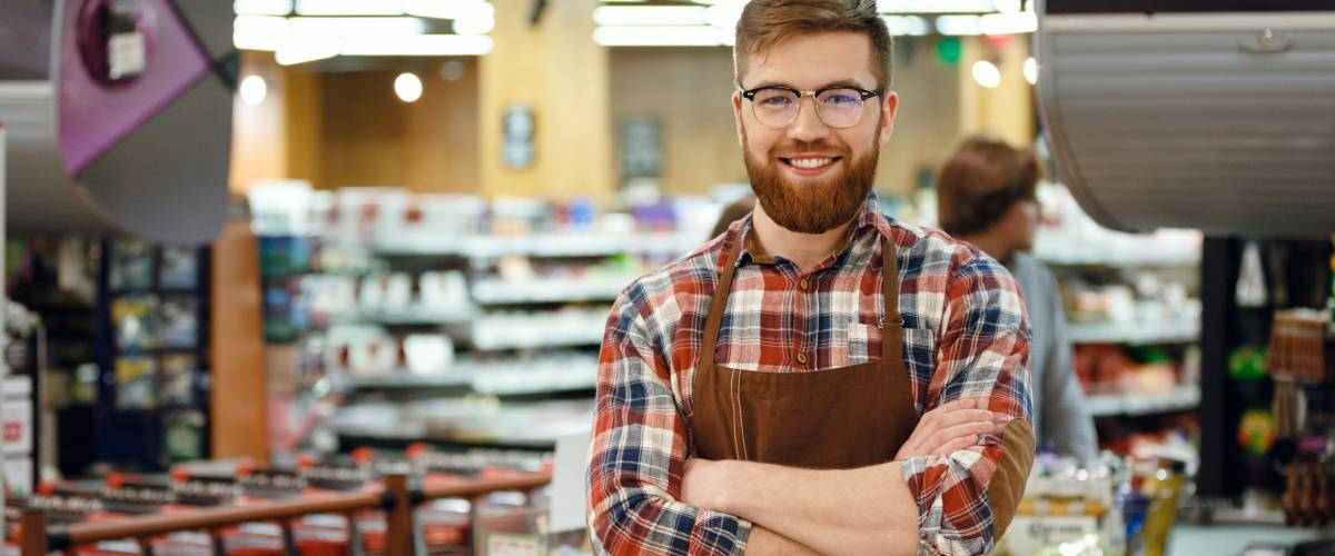 Picture of cashier man on workspace in supermarket shop