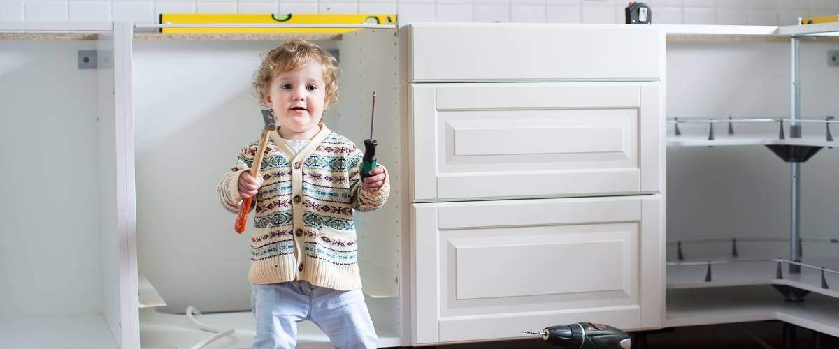 young child helping to install kitchen in family home