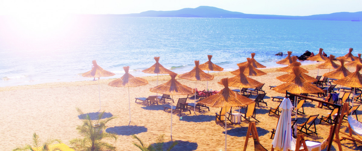 Straw umbrellas on beautiful sunny beach in Bulgaria resort