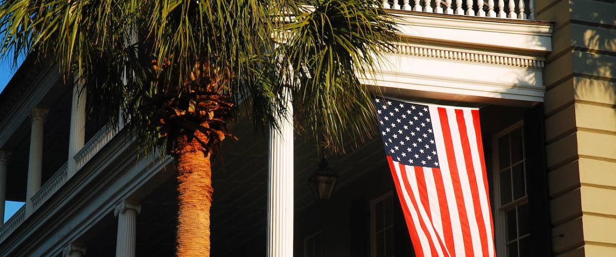A historic Antebellum home flies the American flag.