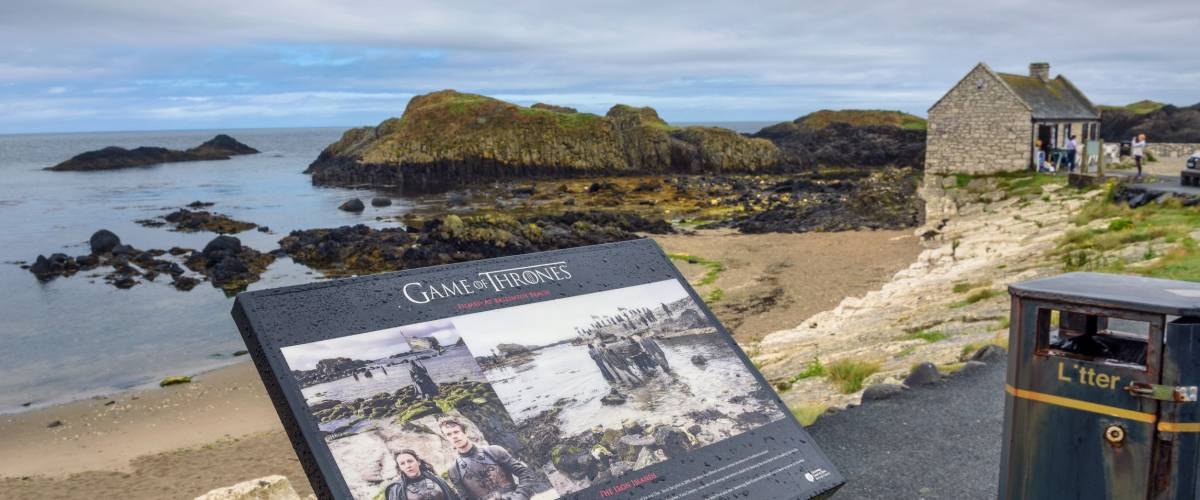 Ballintoy, UK - August 6, 2018 : Visitor information sign with Ballintoy harbor in the background