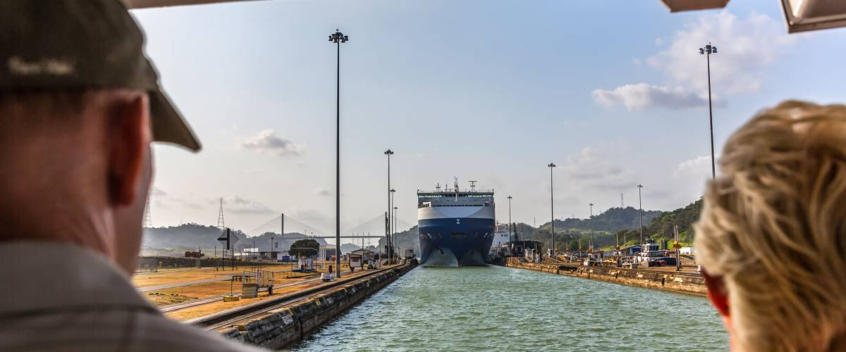 Panama Canal, Panama - Mar 11th 2018 - Tourists looking to a huge ship entering one of the canal locks in a blue sky day in Panama