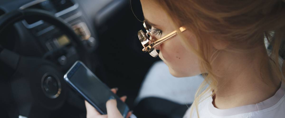 Blond teenager wearing sunglasses on her phone while driving.