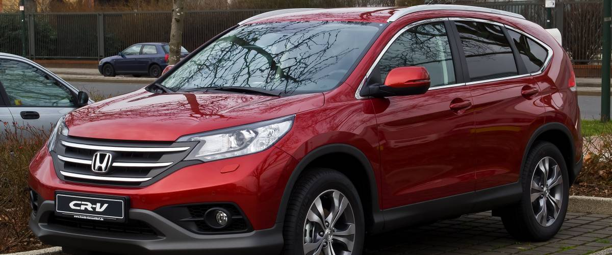 A red Honda CRV, fourth generation, parked in a lot
