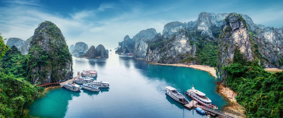 Tourist junks floating among limestone rocks at Ha Long Bay, South China Sea, Vietnam, Southeast Asia.