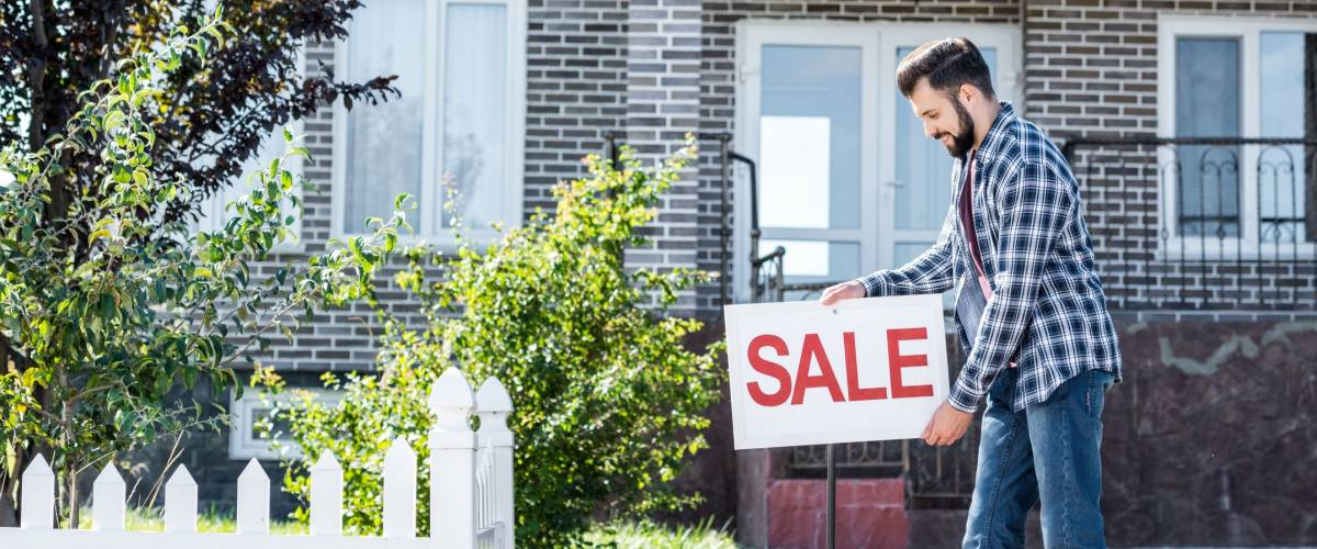 young man with sale board selling his house thanks to low mortgage rates