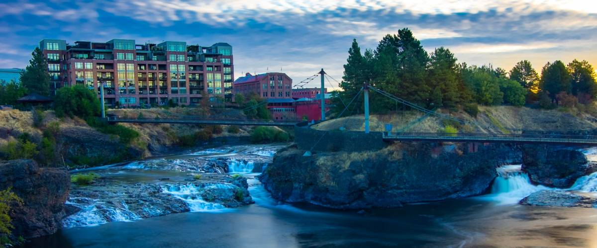 Sunrise over river and falls in downtown Spokane Washington with buildings in the background