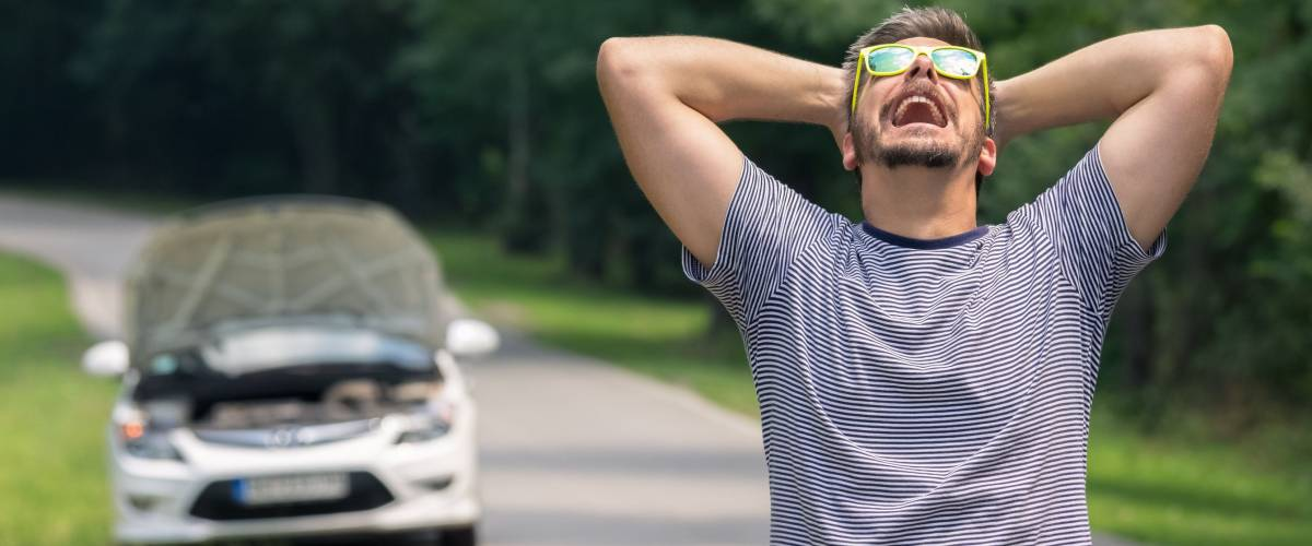 Stressed and frustrated driver pulling his hair while standing on the road next to broken car.