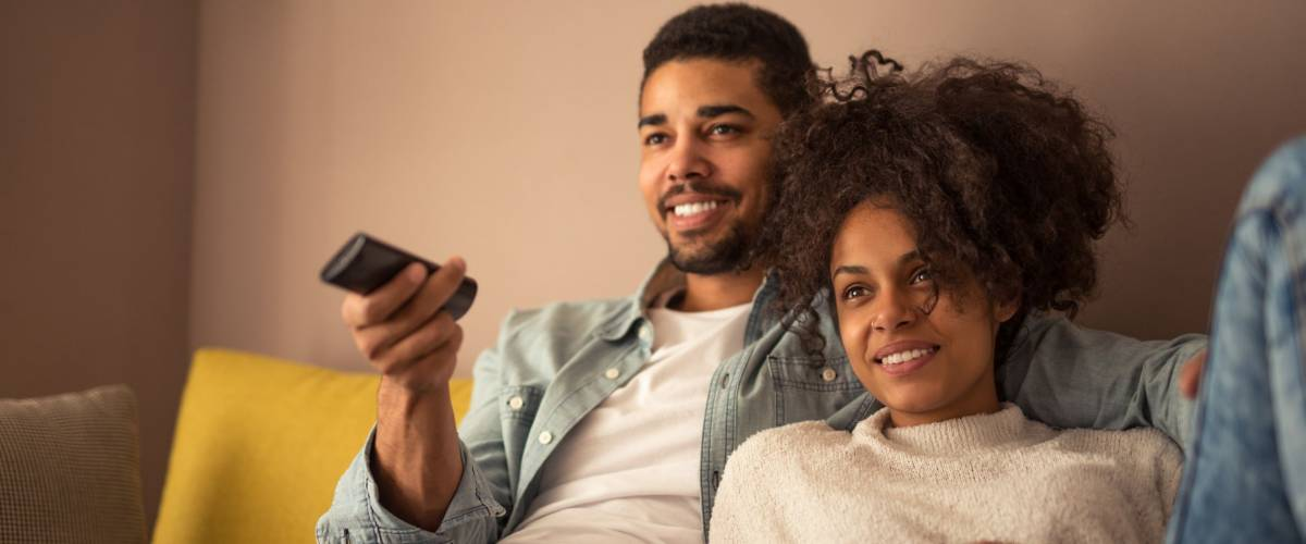 Cropped shot of a young african american couple watching television at home