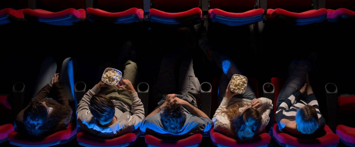 Young people sitting at the cinema, watching a movie and eating pop corn, top view