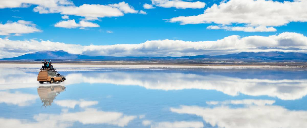 Car with happy people driving on the mirror surface of Salar de Uyuni in Bolivia with clouds reflection