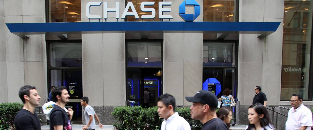 People walking by Chase Bank, owned by JPMorgan Chase & Co.