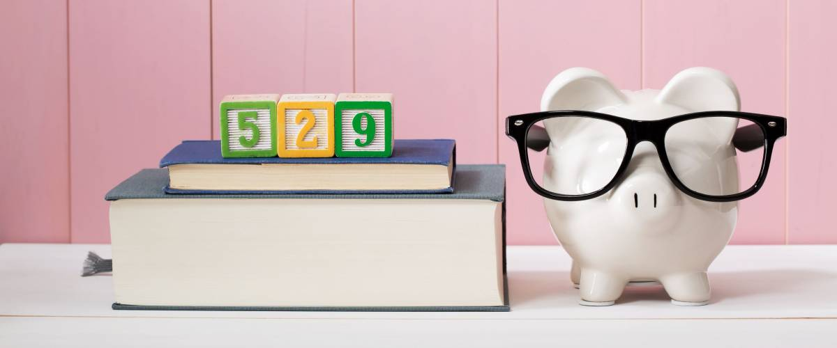 529 in alphabet blocks sit on top of textbooks next to piggy bank wearing eyeglasses