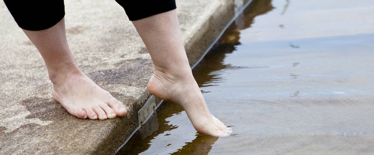 Woman dipping toes into water