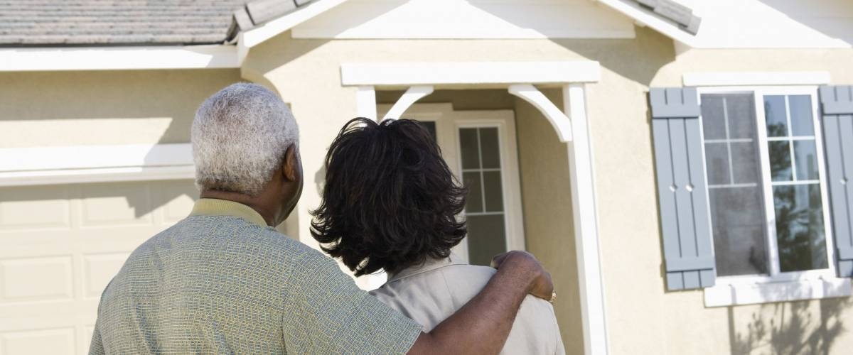 Rear view of African American couple standing in front of new house