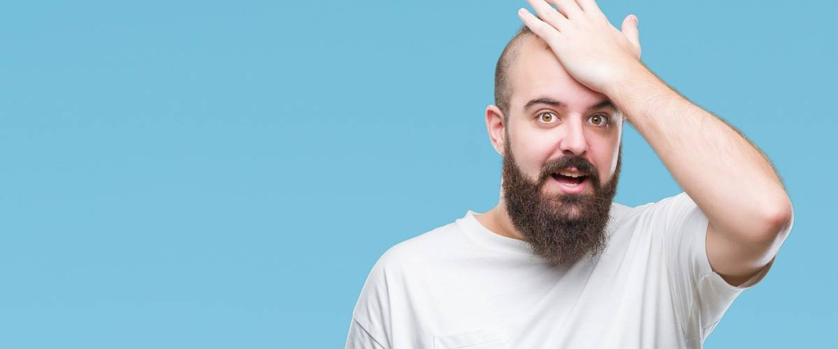 Young caucasian hipster man wearing casual t-shirt over isolated background surprised with hand on head for mistake, remember error. Forgot, bad memory concept.