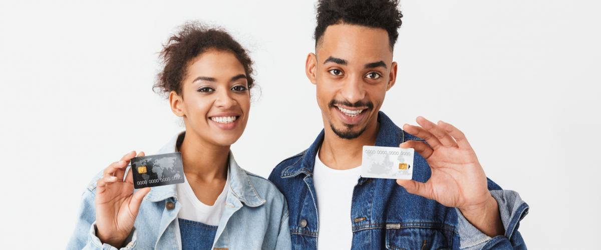 smiling couple holding up two credit cards