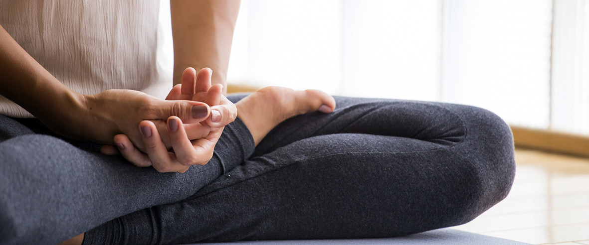 Woman meditating indoors crossed legs