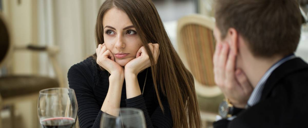 Young woman making an exasperated expression gesture on a bad date.