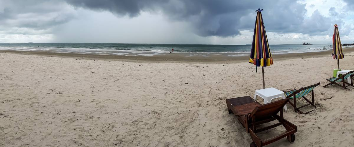 A panorama shot of a beach with incoming rain storm.