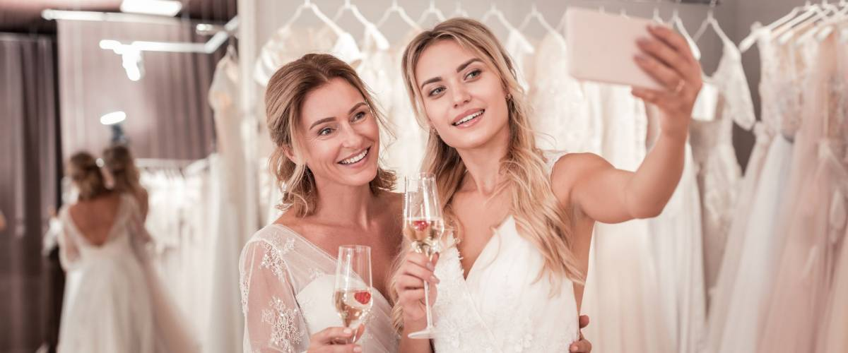 Joyful bride holding glasses with sparkling wine while taking a selfie together