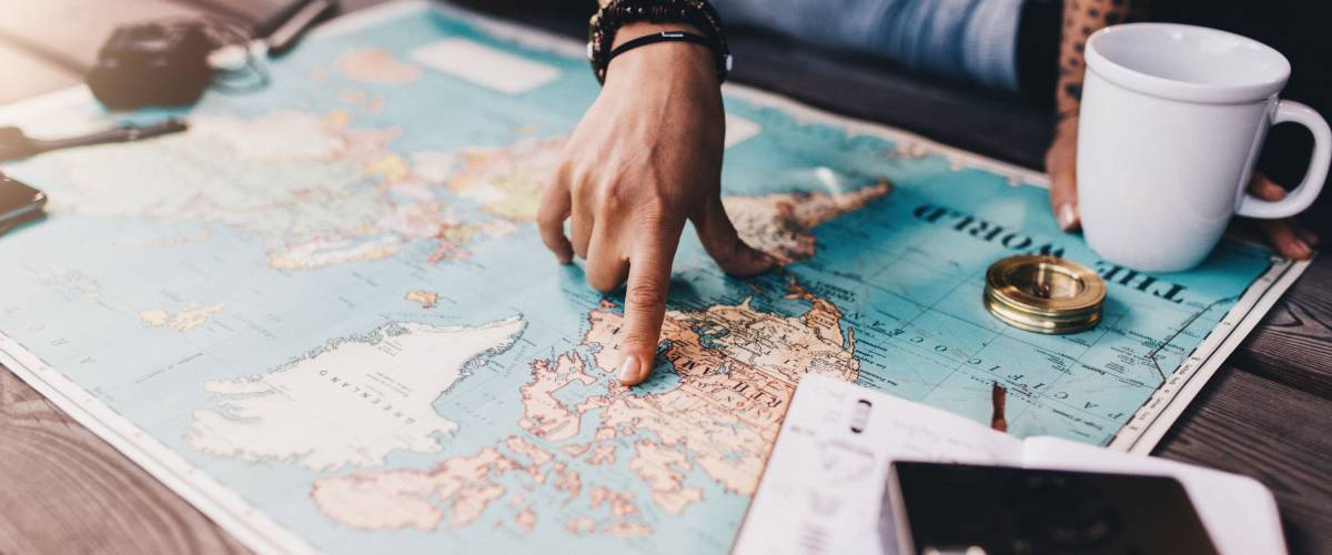 man pointing at map of the world