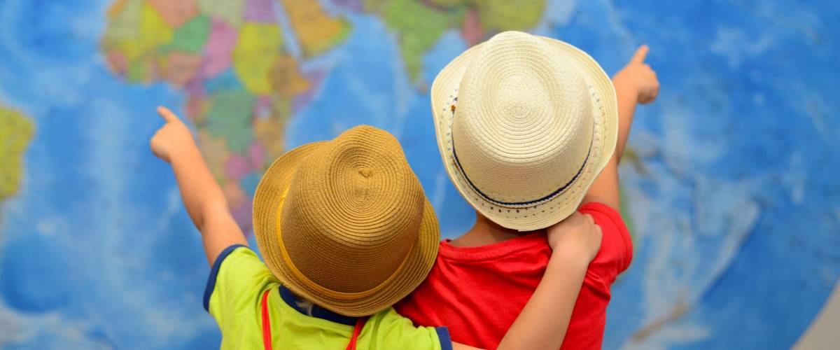 Two children who are siblings point at a world map