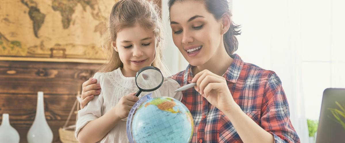 mom and young daughter look at globe