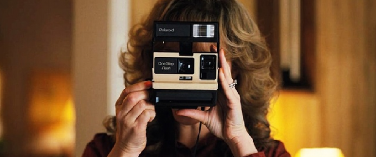 Mom on Stranger things holding polaroid camera