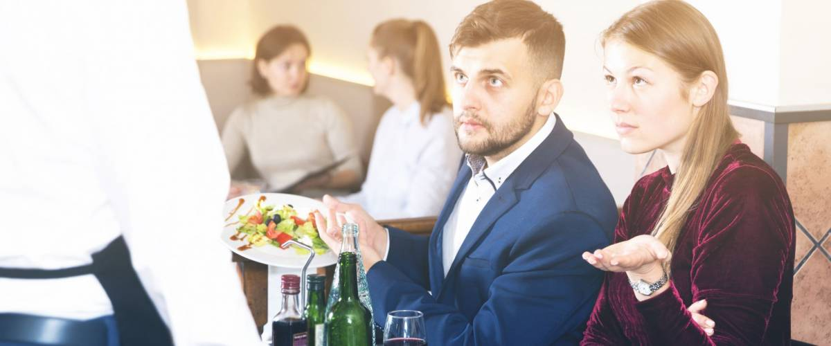 Young couple expressing dissatisfaction with food at restaurant