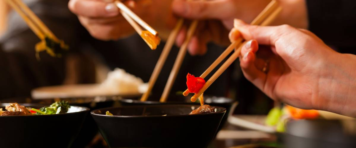 people eating out of a bowl with chopsticks