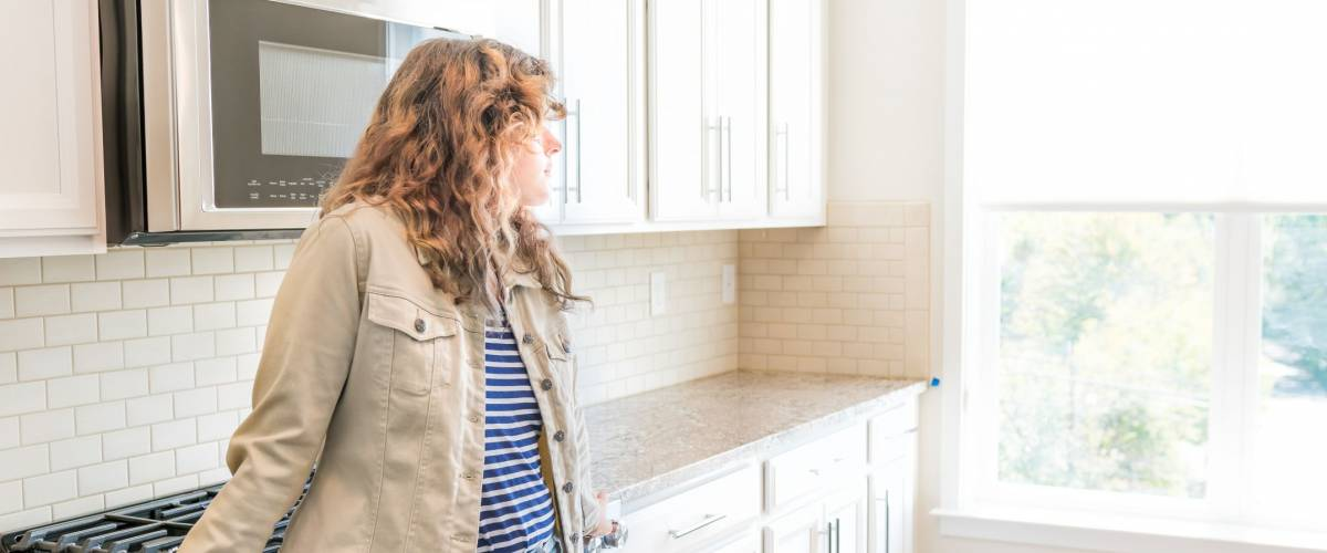 One young woman standing in kitchen in clean, modern, white home design before move-in