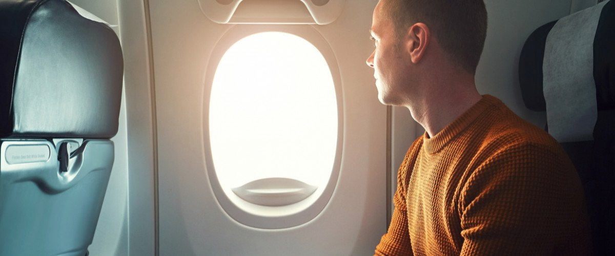 Curious young traveler looks out window of airplane