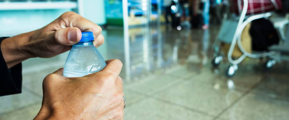 a man's hands opening a water bottle at an airport