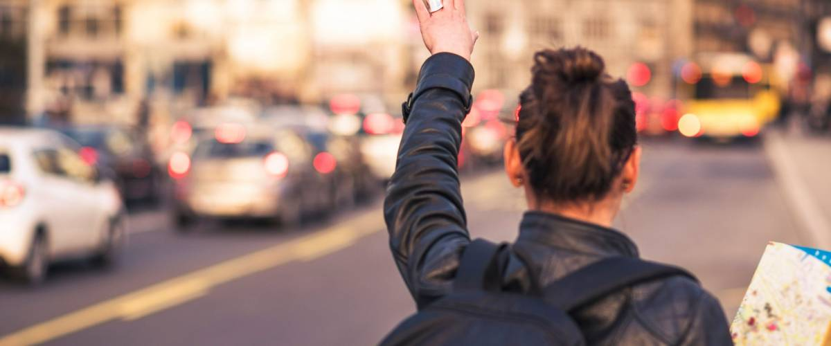 Woman tourist in a foreign city trying to hail a cab