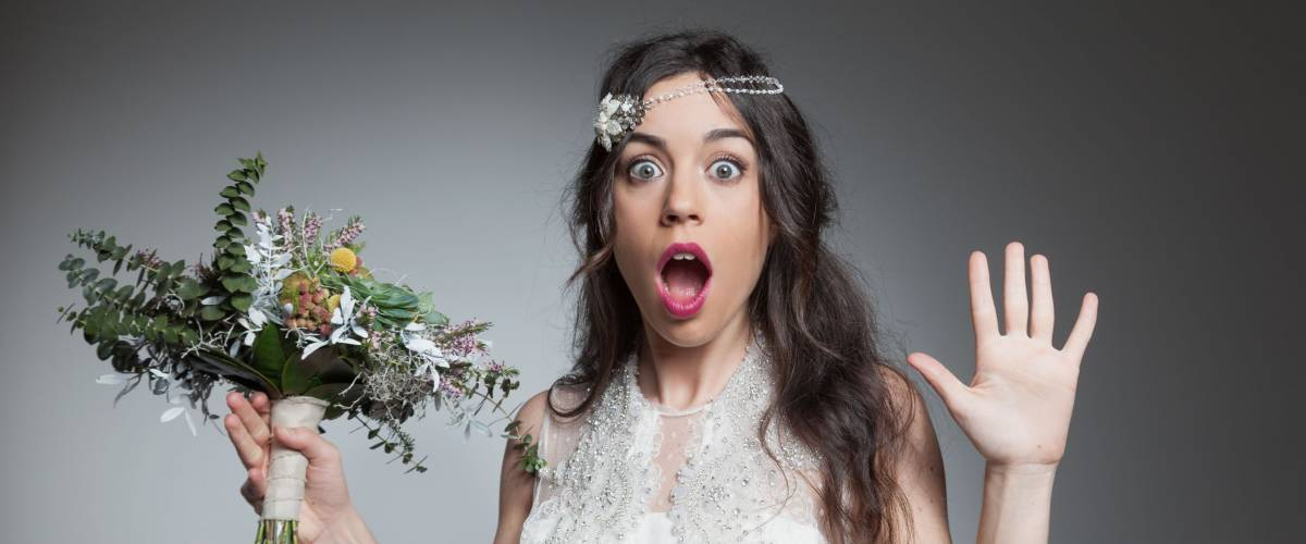 Surprised bride holding flowers bouquet
