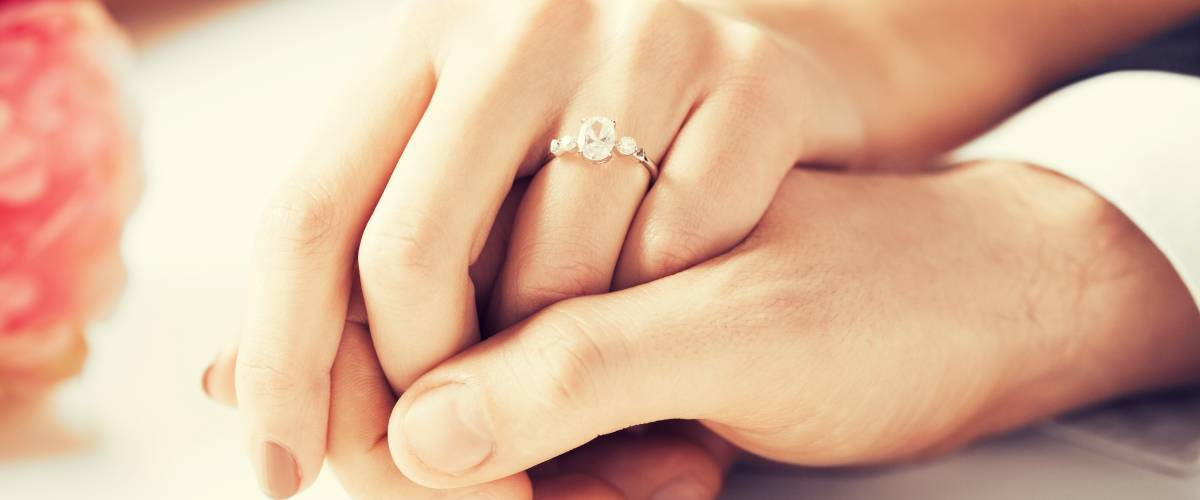 up close engagement ring man and woman holding hands