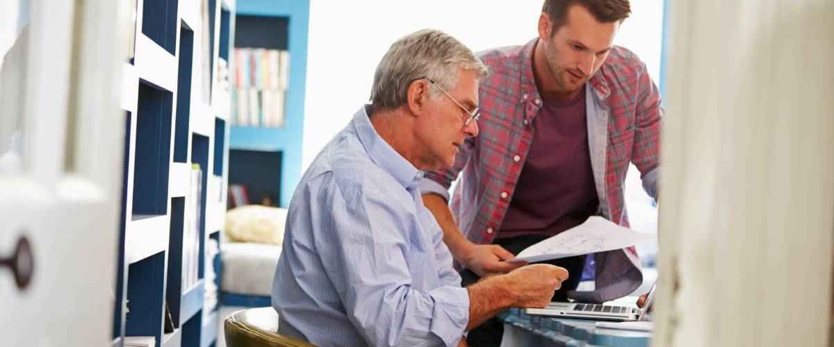 adult son helping his elderly father sort out bills and finances
