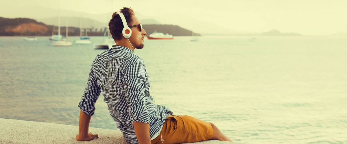 stylish young man in a shirt and shorts and sneakers listening to music in headphones on a beach