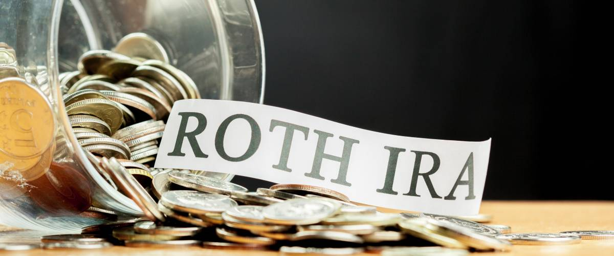Roth IRA coins in a jar, saving for retirement concept