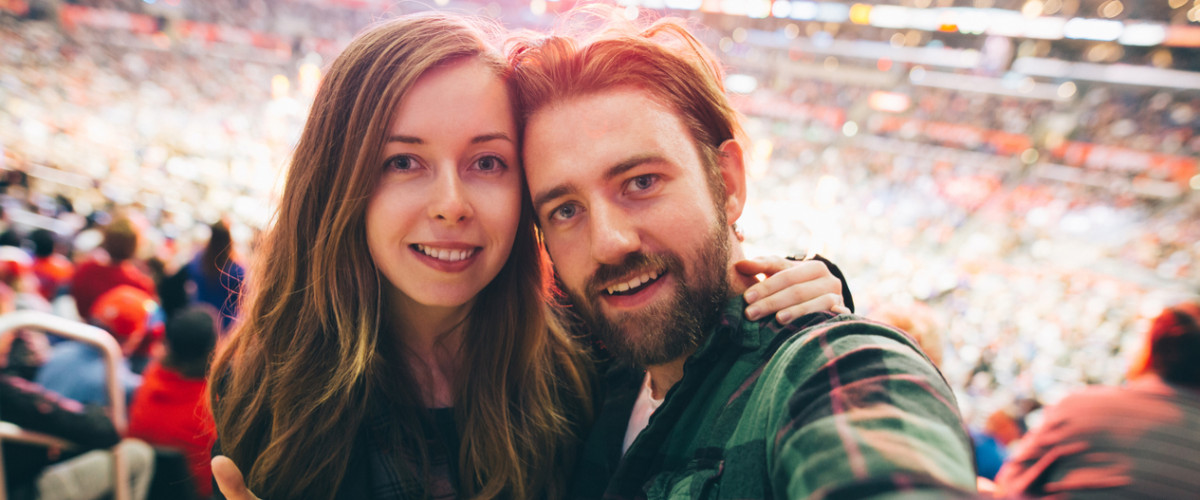 Couple at a sporting event taking a selfie