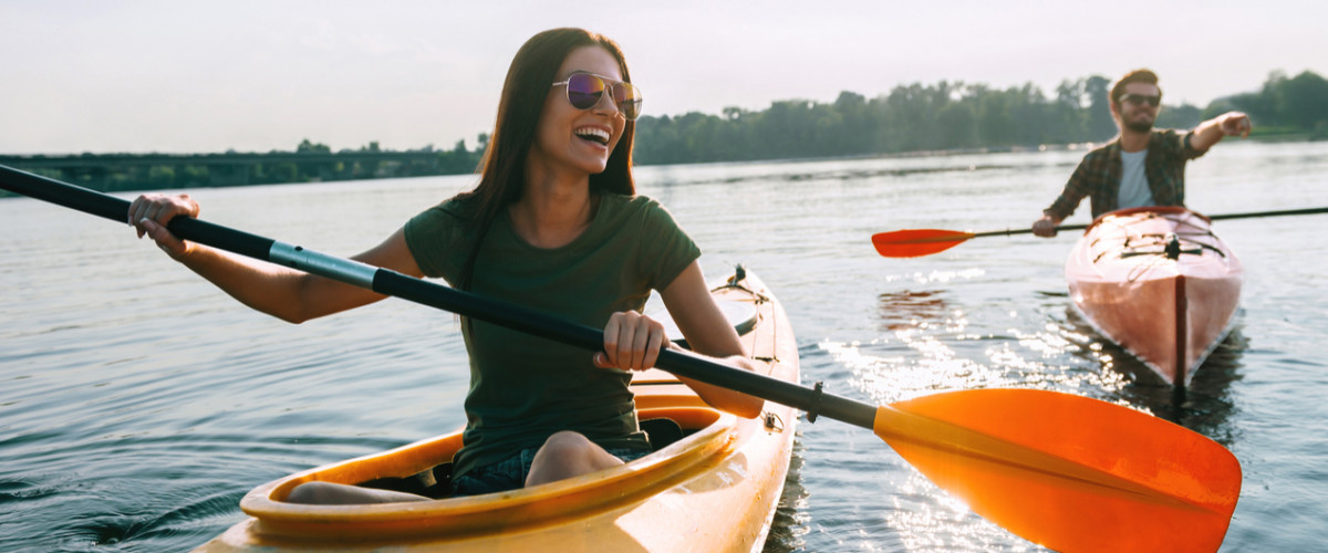 Couple kayaking together. Young couple kayaking on lake together and smiling.