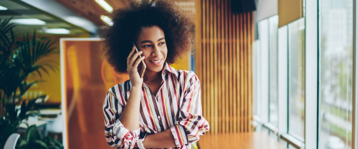 Positive african american young woman standing in modern office and calling on smartphone device.Cheerful dark skinned hipster girl dressed in casual wear talking with friends on mobile phone
